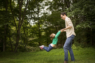 Side view of man playing with daughter in field - CAVF01694