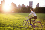 Side view woman cycling in Central Park in city - CAVF01739