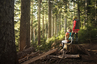 Man sitting while woman standing on tree trunk at forest - CAVF01793