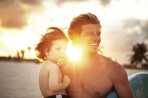 Father and son looking away while standing at beach - CAVF01820