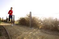 Woman running on road against bright sky - CAVF01940