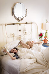 Cheerful friends on bed at home - CAVF02084