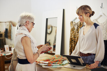 Senior woman paying after shopping in boutique store - CAVF02162