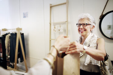 Happy senior woman shopping in store - CAVF02165