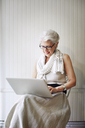 Senior woman using laptop computer while sitting on chair in store - CAVF02177