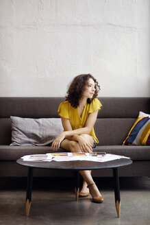 Businesswoman looking away while sitting on sofa in office - CAVF02195