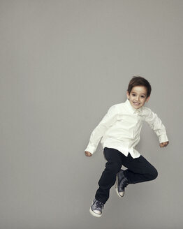 Playful boy jumping against gray background - CAVF02243