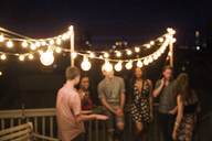 Friends talking while standing by railing on building terrace at night - CAVF02261