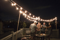 Cheerful friends enjoying drinks on building terrace at party - CAVF02264