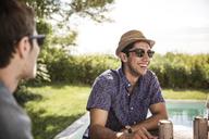 Happy friends sitting in backyard at poolside - CAVF02267