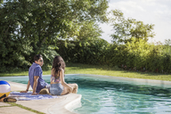 Couple talking while sitting at poolside - CAVF02273