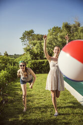 Cheerful friends playing with ball in backyard on sunny day - CAVF02279