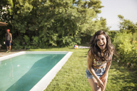 Portrait of cheerful woman in backyard on sunny day - CAVF02282