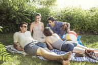Happy friends talking in backyard on sunny day - CAVF02285