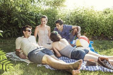 Happy friends talking in backyard on sunny day - CAVF02285