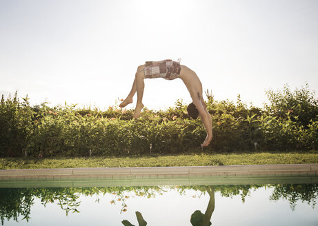 Man somersaulting into swimming pool against clear sky - CAVF02288