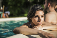 Thoughtful woman looking away while standing in pool with friend - CAVF02300