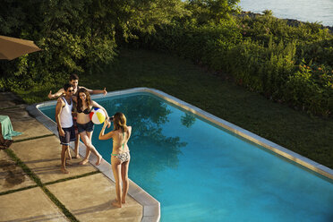 High angle view of woman photographing friends at poolside - CAVF02309