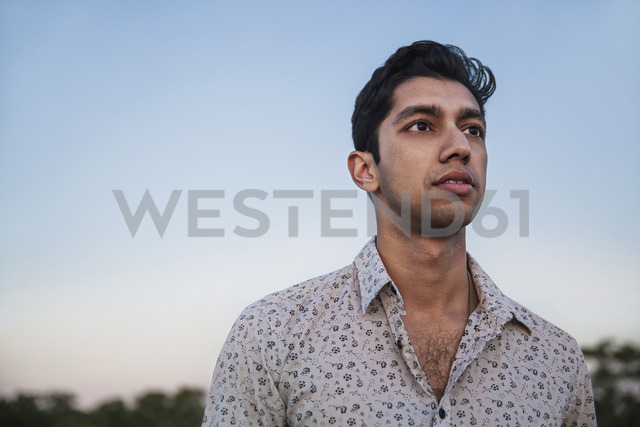 Man looking away while standing against clear sky during sunset - CAVF02318