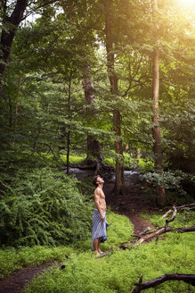 Side view of man looking up while standing in forest - CAVF02351