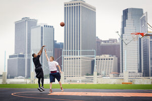 Male athletes practicing basketball in court against buildings - CAVF02360