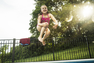 Low angle view of girl jumping in swimming pool - CAVF02375