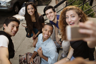 High angle view of woman taking selfie with friends while sitting on steps - CAVF02393