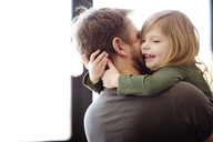 Happy father embracing daughter at home - CAVF02399