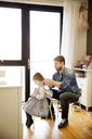 Father tying daughter's hair at home - CAVF02405