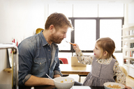 Daughter feeding father at home - CAVF02417
