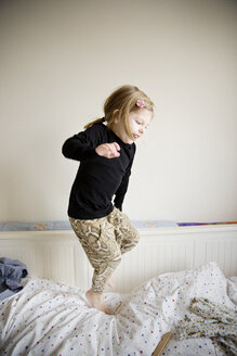 Playful girl jumping on bed at home - CAVF02420