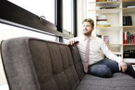 Man looking away while sitting on sofa at home - CAVF02435