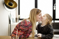 Girl kissing mother while sitting at table in home - CAVF02441