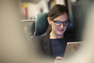 Happy businesswoman using tablet while traveling in subway train - CAVF02468