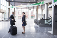 Side view of businessman and businesswoman standing at subway station - CAVF02480