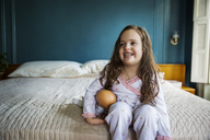 Smiling girl looking away while sitting on bed at home - CAVF02546