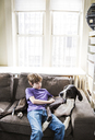 Boy with dog relaxing on sofa at home - CAVF02600