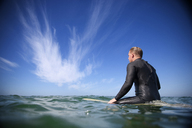 Rear view of man sitting on surfboard in sea against sky - CAVF02648
