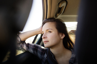 Woman looking away while sitting in car - CAVF02747