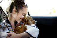 Woman embracing dog while sitting in car - CAVF02750