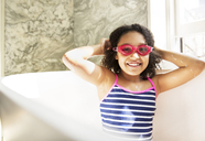 Portrait of cheerful girl wearing swimming goggles while sitting in bathtub - CAVF02822