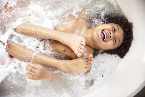 High angle view of cheerful boy enjoying in bathtub - CAVF02825