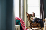 Happy mother carrying baby girl while sitting on chair at home - CAVF02840