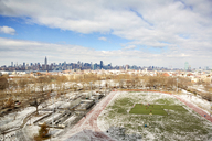 Scenic view of snow covered field and cityscape against cloudy sky - CAVF02846