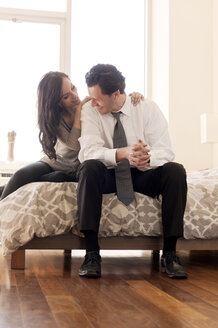 Happy couple sitting on bed at home - CAVF02855