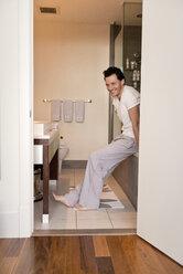 Cheerful man sitting on bathtub in bathroom - CAVF02858