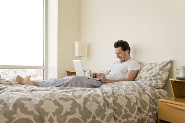Side view of happy man using laptop on bed at home - CAVF02861