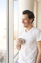 Smiling man drinking coffee and looking though window - CAVF02867