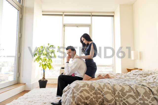 Side view of couple relaxing on bed in brightly lit bedroom - CAVF02873 - Cavan Images/Westend61