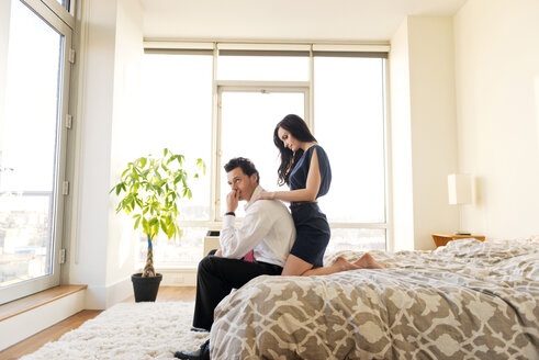 Side view of couple relaxing on bed in brightly lit bedroom - CAVF02873